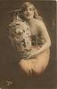 long haired model in off-shoulder dress & long string of pearls poses to right of large ornamental  vase, holds it on her lap, faces front, looks up