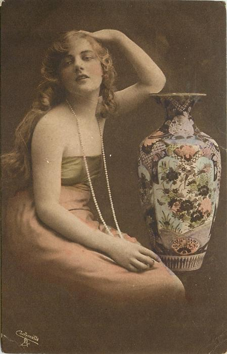 long haired model in off-shoulder dress & long string of pearls poses to left of large ornamental  vase,  left elbow rests on top of vase, right hand in her lap, she looks left