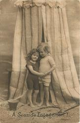 A SEASIDE ENGAGEMENT!  boy & girl in front of striped bathing tent