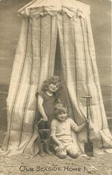 OUR SEASIDE HOME!  boy & girl in front of striped bathing tent