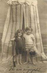 WE ARE ENGAGED!  boy & girl in front of striped bathing tent