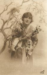 girl in kimona posed next to tree with parrot, bird on branch behind & above, her hands crossed in front of her chest holding flowers, she looks up