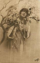 girl in kimona posed next to tree with parrot, bird on branch behind & above, her left hand at left side of face, holding flowers, right hand at chest level holding flowers