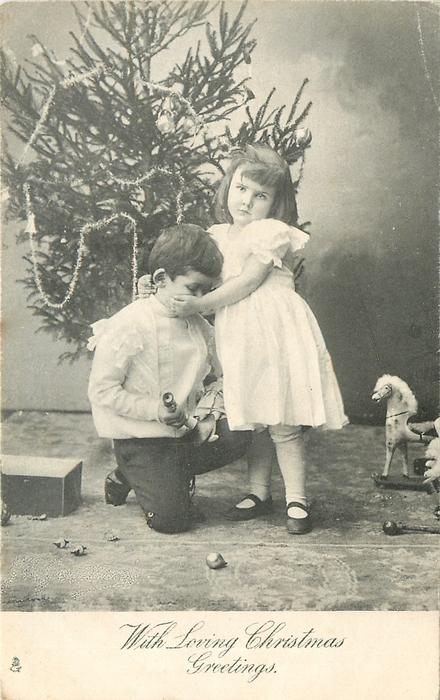 WITH LOVING CHRISTMAS GREETINGS  girl caresses kneeling boy in front of Xmas tree