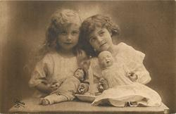 two young girls sit side by side, blonde to left, brunette to right, heads touch, dolls & candle on table in front