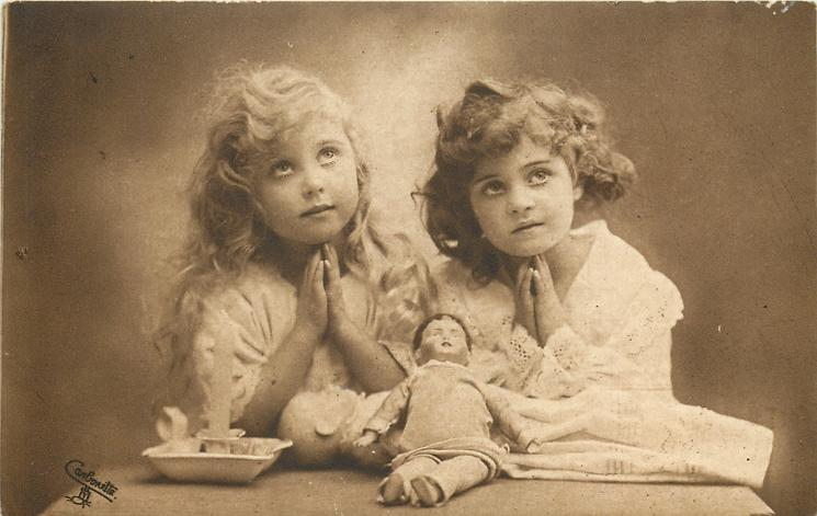 two young girls praying, blonde to left, brunette to right, dolls & candle on table in front