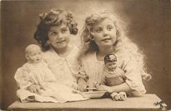 two young girls sit side by side, blonde to right, brunette to left, each holds doll, blonde girl's hands hold base of candle fronte front