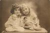 two young girls sit side by side, blonde to right, brunette to left, heads touch, dolls & candle on table in front/right