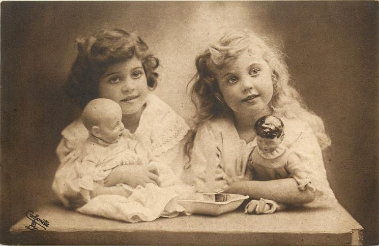 two young girls sit side by side, blonde to right, brunette to left, heads apart, each holds doll, neither girl touches candle front