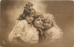 two girls cuddle by boy in the middle