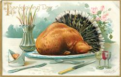 turkey on plate with feathers behind, three wine glasses lower right, roll, two forks, spoon and knife