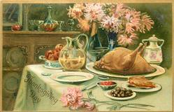 cooked turkey on plate, no feathers, wine jug and two glasses behind turkey along with fruit plate