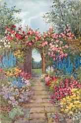 path leads to trellis covered with roses, many coloured flowers on both sides of path