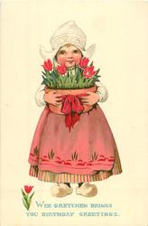 Dutch girl stands holding large pot of tulips
