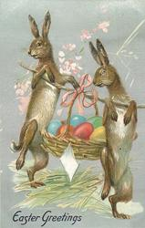 EASTER GREETINGS  two rabbits carry stick with basket of Easter eggs slung on it