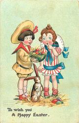 TO WISH YOU A HAPPY EASTER  boy shows bowl of Easter eggs to astonished girl, rabbit below