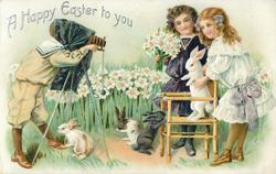A HAPPY EASTER TO YOU  boy takes photo of two girls, one girl holds flowers, the other a rabbit