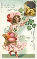 TO WISH YOU A HAPPY EASTER  girl in pink dress has basket of huge eggs on right arm, touches chicks above with left hand