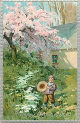 A HAPPY EASTER TO YOU  boy stands in grass holding straw hat, blossom tree & house behind