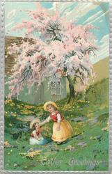EASTER GREETINGS  two girls play in grass, left one sits, right stands, pink blossom tree & house behind