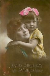 child in yellow dress and pink bow in hair with left arm around mother's neck, both look ahead