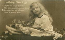 BIRTHDAY GREETINGS girl sitting facing left, looking front hands on lilac on lap