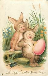 LOVING EASTER GREETINGS  two children dressed as rabbits sit on steps, one paints large egg