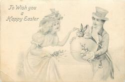 TO WISH YOU A HAPPY EASTER  man holds huge shell with two rabbits peeking out, lady reaches to them