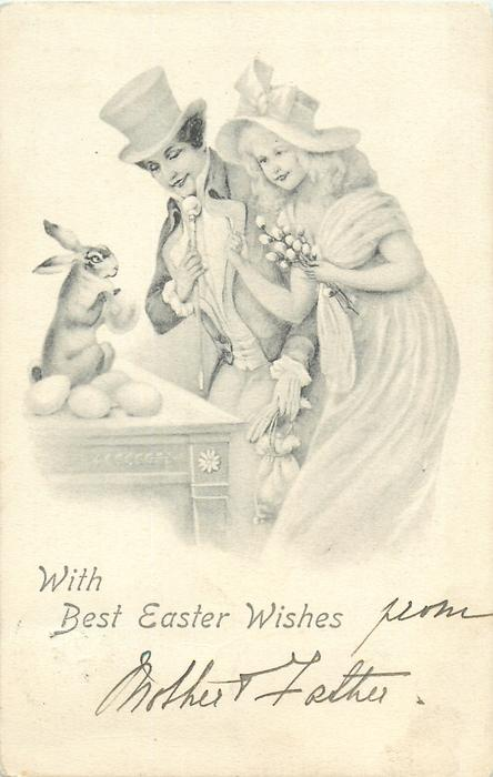 WITH BEST EASTER WISHES  man & woman stand admiring rabbit sitting on table with Easter eggs