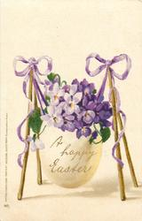 A HAPPY EASTER  egg full of violets suspended from supports at each side, purple ribbons