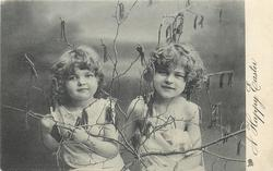 A HAPPY EASTER  two girls with branches & catkins, girl on right has hand behind other girl