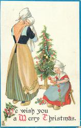 WE WISH YOU A MERRY CHRISTMAS  Dutch mother carries baby, girl sits on stool fixing decorations, tree behind