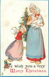 WE WISH YOU A VERY MERRY CHRISTMAS  Dutch girl shows doll to baby in mothers arms, tree behind