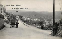 LAXEY  old-style car on left side of road, view of town in distance