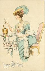 LOVES GREETINGS  lady in blue sits at table champagne glass in hand