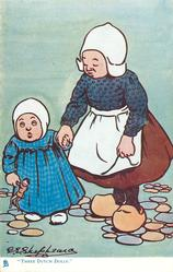 """""""THREE DUTCH DOLLS.""""  two girls stand holding hands, youngest holds small doll"""