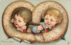 boy on right pushes head & hands through pretzel shaped cooky to pull pig-yail of girl on left
