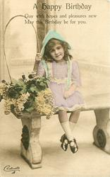 A HAPPY BIRTHDAY girl sits on bench next large basket of flowers, ankles are crossed, she looks front