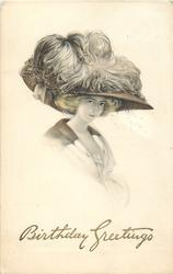 glamorous woman in large decorated hat, corsage not seen, faces right, looks front