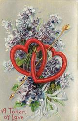 A TOKEN OF LOVE  intertwined hearts, arrow through them, violets behind