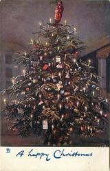 A HAPPY CHRISTMAS tiny Santa at top of heavily decorated Christmas tree