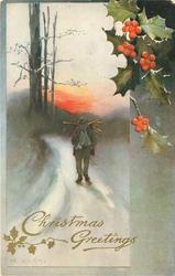 CHRISTMAS GREETINGS  man with sticks across his shoulder walks front on snowy road, trees behind