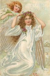 A HAPPY CHRISTMAS  full length angel in swirling white robe holding violet circlet on head, another angel behind left