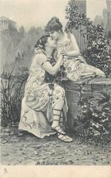 two woman caress on & in front of stone wall, they hold hands & one kisses the others forehead