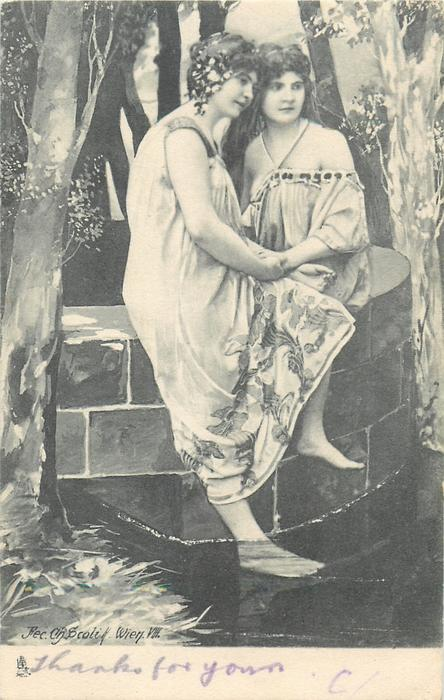 two woman sit on either side of stone wall, one has foot in pool, they hold hands