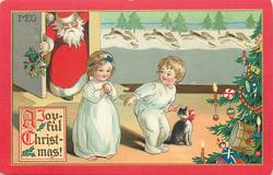 A JOYFUL CHRISTMAS!  Santa comes in door, two children in white night attire & cat, tree far right
