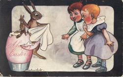 A HAPPY EASTER  two children watch rabbit magician pull baby rabbit out of egg