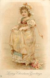 LOVING CHRISTMAS GREETINGS  girl standing facing half left, holding up skirt with both hands, bouquet on floor