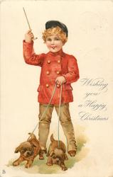 WISHING YOU A HAPPY CHRISTMAS  boy in red jacket holding pair of puppies on leash