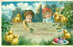 boy & girl stand behind wooden fence exaggerated chicks around & coloured eggs on plate